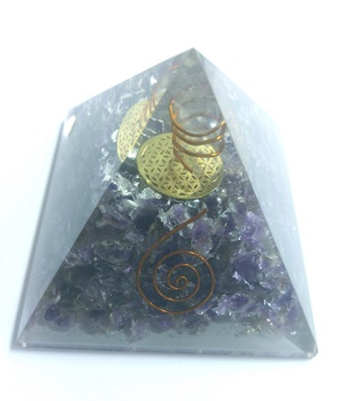 """Orgone Pyramid Amethyst  ORGONITE refers to a mix of crystals and or semi-precious gemstones, metals and resin in a combination that may balance out our life-energy. This natural Earth energy is considered the most powerful energy there is and the frequency it resonates is considered the """"heartbeat"""" of our planet.  The organic materials absorb the vital, orgonic energy, while the non-organic materials disperse it back in all directions.  Crystals & precious gemstones are electrically charged by the resin, that contracts them. Hence, the powerful healing effects of the crystals are magnified in an orgone pyramid.  Benefits of Orgone Pyramids:  When placed in your work, living or sleeping space, the orgone pyramids have the ability to clean the energies in the room & protect the individuals from EMF radiation. Laboratory research shows that living body cells strengthen their immunity & reach optimal physical & psychological health.  This includes:  Help insomnia & improve sleep & vivid & pleasant dreams  Improves immunity & resistance to illness, enhances energy & overall wellness  Protection from EMF radiation caused by electronic devices  Create a peaceful environment by enhancing positive energies  Access deeper meditative states, strengthen visualisations & intentions  Project high vibrational energies the minimise stress  Assists in imbalances as if they know what one needs on a spiritual level.   There are many Orgone Pyramids for many uses."""