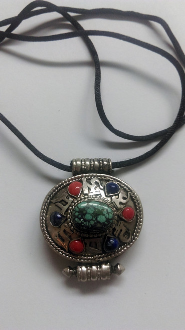 White metal Tibetan Necklace with lapis, torquois & red coral inserts with mantra symbols on a leather cord.