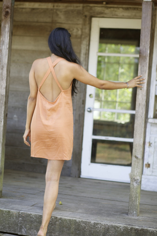 Amber Nightie | Caramel HAZEL MOON Image of a woman stepping barefoot onto a porch wearing the Amber Nightie in Caramel from Hazel moon, a piece of natural fiber clothing.