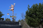 Party Pig Weathervane right angle view on blue sky background.