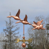 two geese and a flying pig weathervane left side view on gray sky background.