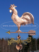 cockerel weathervane side view on blue sky background