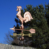 rooster weathervane left angle view on blue sky background