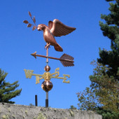 dove weathervane carrying an olive branch left front angle view on blue sky background