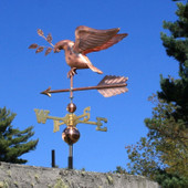 dove weathervane carrying an olive branch left rear view on blue sky background