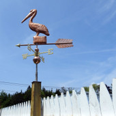 pelican weathervane left side view on fence post mounted and blue sky background