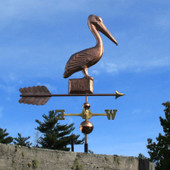 Pelican on a Post Weathervane right side view on blue sky background