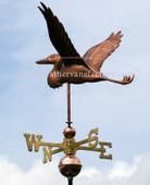 flying heron weathervane side view on blue sky image