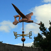 Large Copper Stork and Baby Weathervane left side view on blue and cloudy sky background