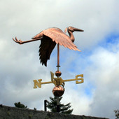 flying heron weathervane with the wings down right rear view on cloudy and blue sky background