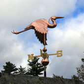 flying heron weathervane with the wings down right back side view on cloudy and blue sky background