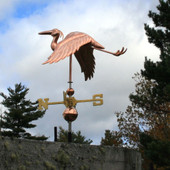 flying heron weathervane with the wings down left under side view on cloudy and blue sky background