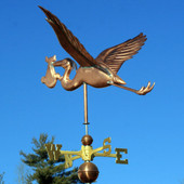stork with baby weathervane left rear view on blue sky background