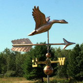 flying goose weathervane right side angle on blue sky with trees background