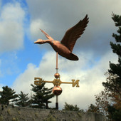 large flying goose weathervane left side view on blue and cloudy sky background