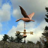 Flying Goose Weathervane left rear view on blue and cloudy sky background
