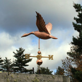 large flying goose weathervane left side view on stormy sky background