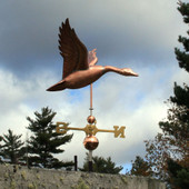 large flying goose weathervane right side view on stormy sky background