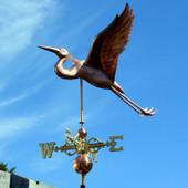 Heron weathervane left side view on blue sky background.