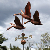 large flying three geese weathervane left side view on stormy sky background