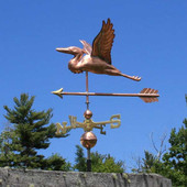 flying heron weathervane with arrow left side view on blue sky background