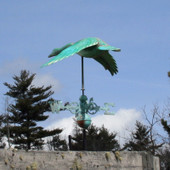 Flying Goose Weathervane shown in patina green with the wings down rear view on blue sky background