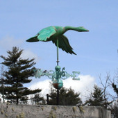 Flying Goose Weathervane shown in patina green with the wings down right angle view on blue sky background