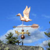 Flying Duck Weathervane left side view on blue and cloudy sky background