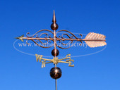 large scrolled arrow weathervane side view on blue sky background image