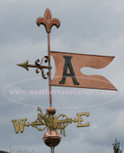 banner weathervane shown with letter A left side view on stormy background with scrolled directionals and fleur de lis top