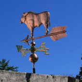bull weathervane left rear view on blue sky background