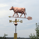 Cow Weathervane left side view on gray sky background