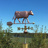 walking cow with horns weathervane right side view on a blue sky background