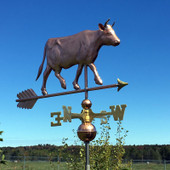 walking cow with horns weathervane right front view on a blue sky background