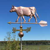 walking cow with horns weathervane left side view on a blue sky background