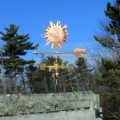 sun weathervane left side view on blue sky background