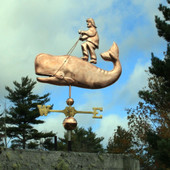 Man riding a Whale Weathervane left side view on blue cloudy background