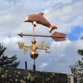 Photo of our copper handmade dolphin weathervane on an arrow with a cloudy background. This dolphin Weathervane is made to order from The Weathervane Factory.