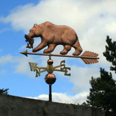 bear with fish weathervane side view photo on blue sky