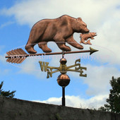 bear with fish weathervane right side view on cloudy sky background
