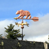 small bear weathervane left side view on blue and cloudy sky