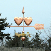 Two Hearts Weathervane left side view on blue sky background.