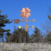 small four leaf clover weathervane on blue sky background, right side view