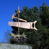 large saw and hammer weathervane left side view on blue sky background