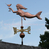 mermaid weathervane with martini glass left side view on blue sky background