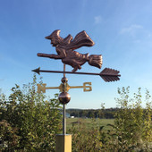 witch riding a broom weathervane left side view on blue sky background