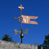 banner weathervane with cross and fleur de lis left side view on blue sky background