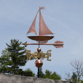 sailboat weathervane with scrolled directionals and left  front side view cloudy sky background