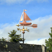 Little sailing ship weathervane left side view on blue sky background
