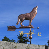 Large Copper Wolf Weathervane standing on a rock while howling, right side view on blue sky background